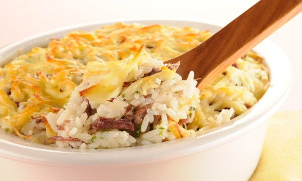 Refogue o arroz com o óleo e a cebola, junte a água. Quando o arroz estiver quase cozido, acrescente a carne seca desfiada e deixe secar o líquido. Distribua em um refratário e cubra com o queijo c…