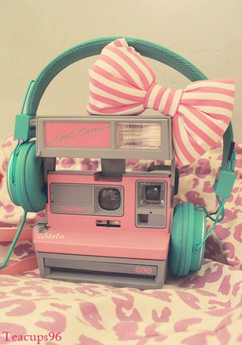 Vintage camera, blue headphones, and striped pink bow.