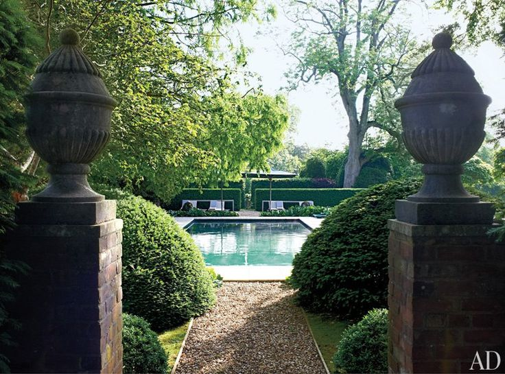 Chaise longues border the pool at designer Anouska Hempel's English country estate.