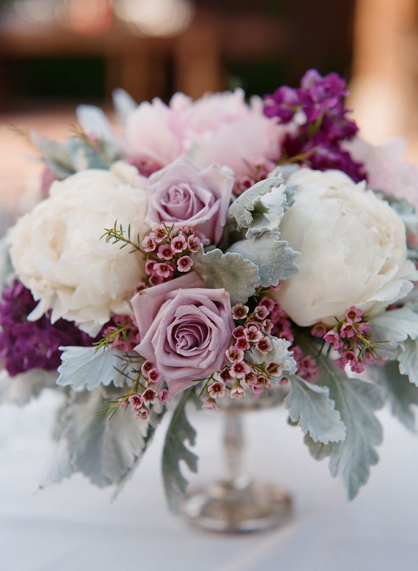 A white peony, dusty miller, and lavender rose wedding centerpiece.