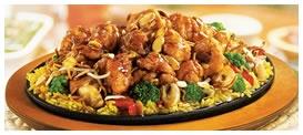 Crispy Orange Chicken: Crujientes cubitos de pollo rebozados y fritos , bañados en nuestro original glacé de naranja sobre una cama de arroz pilaf, acompañados de zanahoria, brotes de brócoli, dientes de dragón, champiñones, pimiento rojo, decorado con almendras y fideos chinos. Foto referencial.