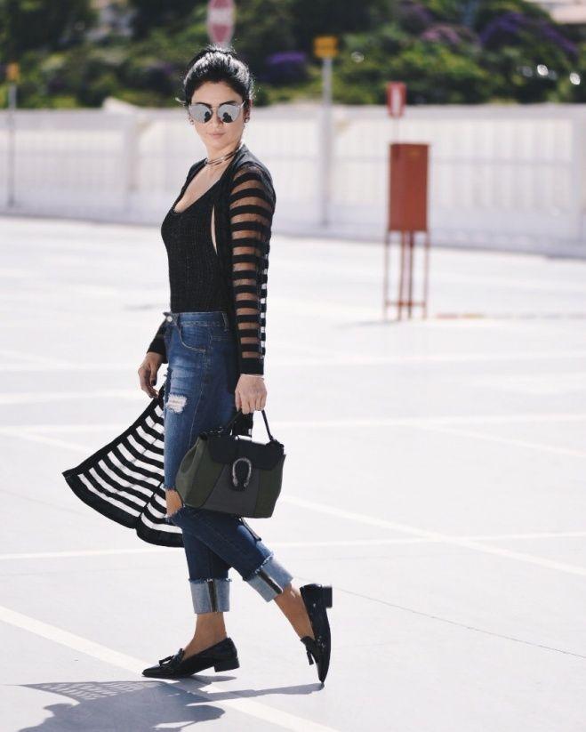 Look de Constanza Fernandez com maxi cardigã de lurex com um body levemente brilhoso, calça jeans rasgada, bolsa estruturada na cor da moda – verde militar – e um mocassim preto em verniz.