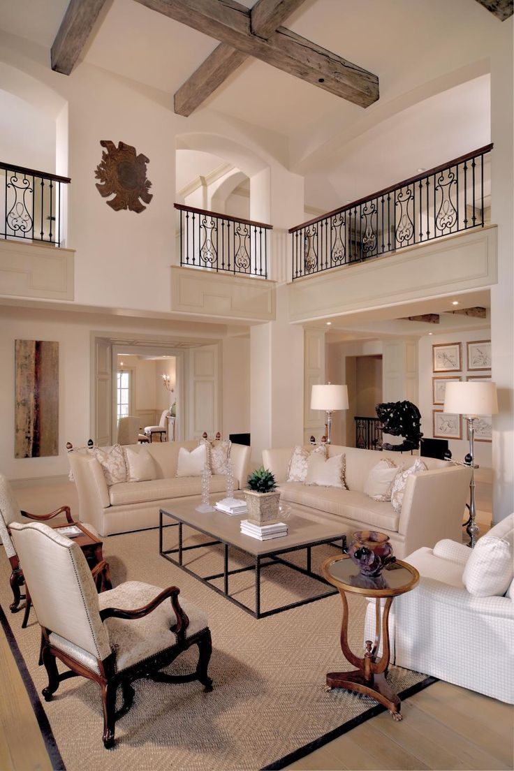 Traditional furniture pieces pair with more clean-lined picks for a transitional look in this beautiful living room. Two-story ceilings and a light color palette make the room feel open and spacious.