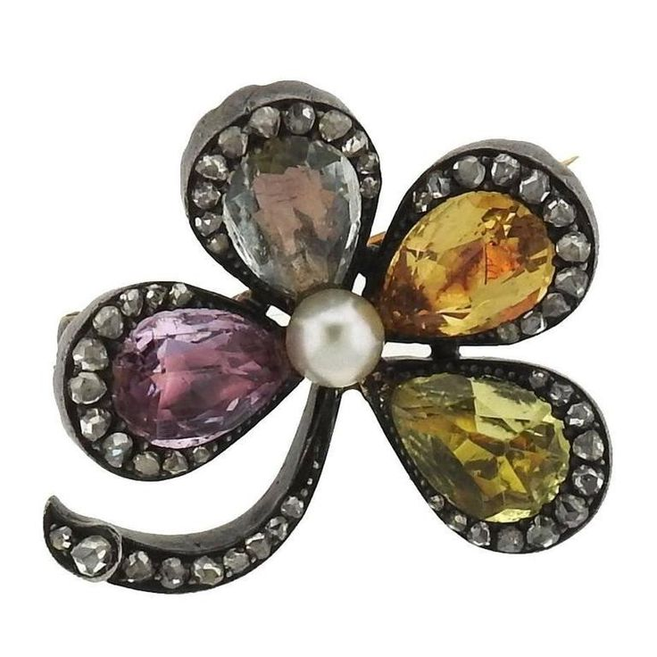 An 18k gold and silver brooch pin set with multi color sapphires, rose cut diamo...