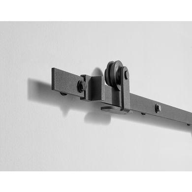 Simplifiez vos ouvertures avec ce système coulissant Harlem en applique pour porte en bois. L'ensemble en acier noir, sobre et discret, fonctionne grâce à un roulement à billes et une butée de porte.