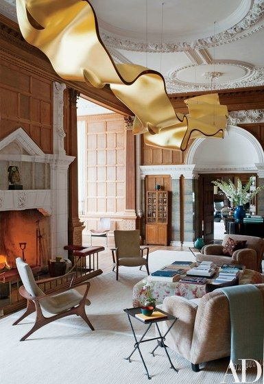 The library's rippling light, suspended from the original plasterwork ceiling, is by Ingo Maurer. The vintage lounge chairs are by Vladimir Kagan; the velvet club chairs were custom made, and the large ottoman is covered in a Sultanabad carpet | archdigest.com