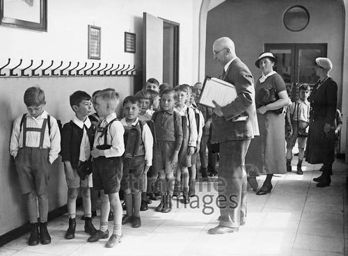 Volksschulkinder in Berlin, 1933 Timeline Classics/Timeline Images #30er #schwarzweiß #Fotografie #photography #historisch #historical #traditional #traditionell #retro #nostalgic #Nostalgie #Schule #School #Schüler #Lernen #Studieren #Bildungseinrichtung #Unterricht #Schulzeit #Ausbildung #Lehrer #Volksschule #Reihe #aufgereiht #Schuluniform #Mitschüler #Schulgebäude #Garderobe #Garderobenhaken