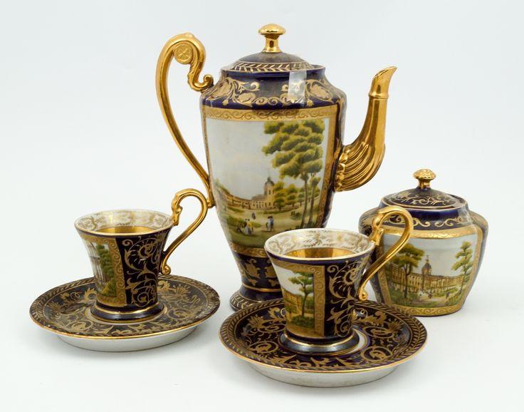 Een kobaltblauw deels verguld theeserviesje met landschapsdecor, bestaande uit theepot, suikerpot en twee kop-en-schotels, Sèvres-stijl