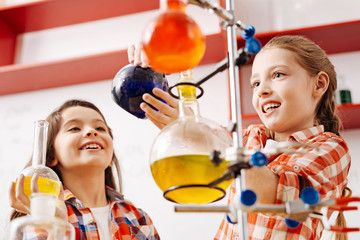 Cute joyful girls using scientific equipment
