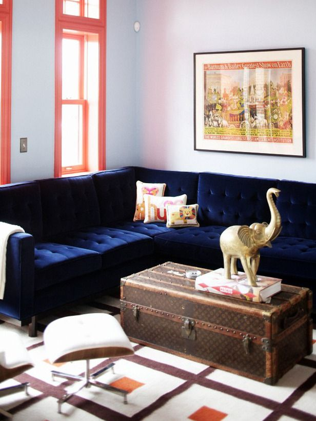 Summery coral paint on the trim of this family room contrasts perfectly with the gorgeous blue sofa.