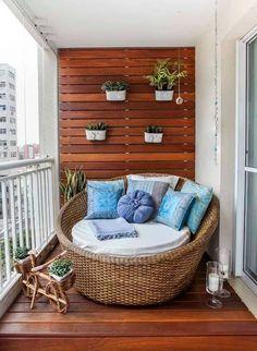 Sacada com piso e parede em deck de madeira com pufe moderno