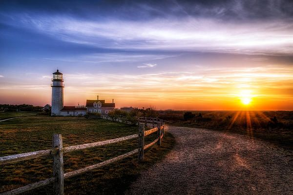 """Cape Cod's oldest lighthouse, locally known as the Highland Light, is officially named """"Cape Cod Light"""" on the NOAA nautical chart for the region. It sits perched 120 feet above the ocean in the Highlands of Truro. Its beam shines 174 ft. above sea level to give mariners warning of the treacherous sandbars off this shore."""