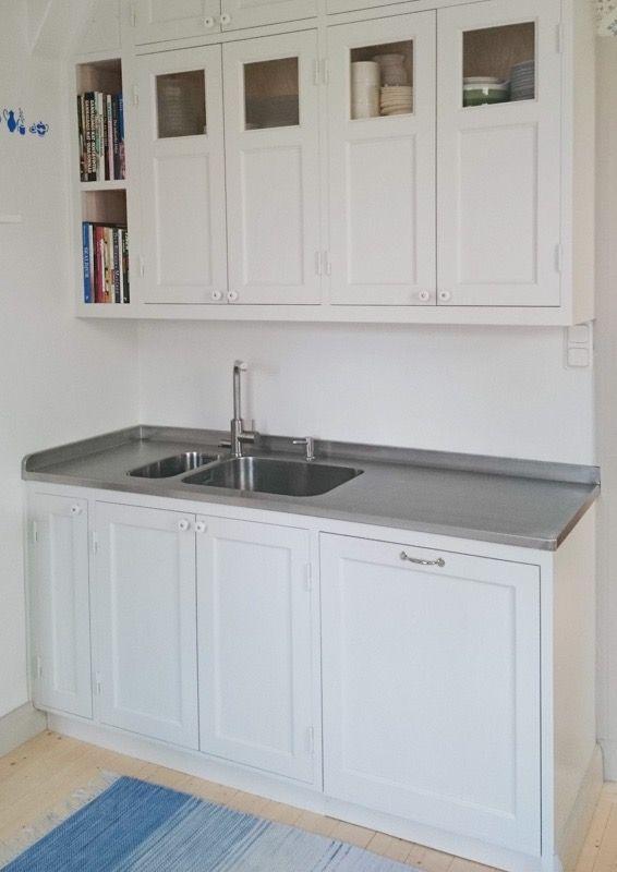 Tidlöst vit kök med rostfri diskbänk.