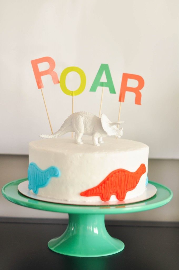 A store-bought dinosaur birthday cake with Oh Joy for Target topper and a painted dinosaur. Dinosaur party ideas.