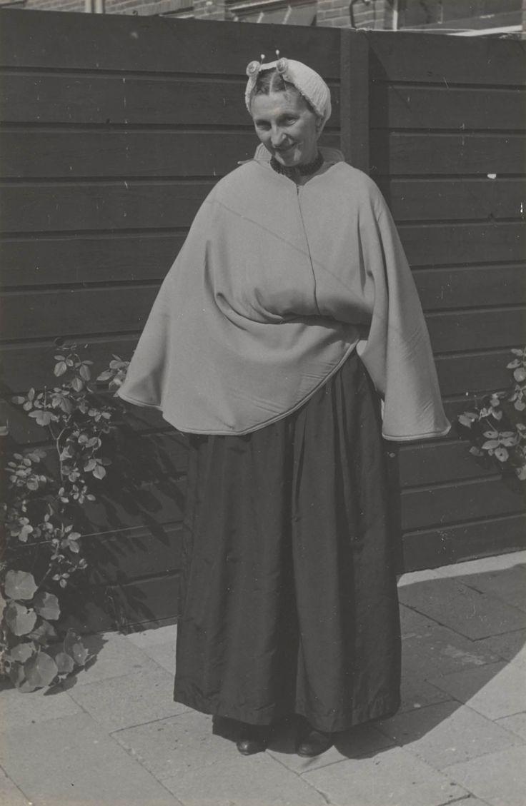 Vrouw in Scheveningse streekdracht. De vrouw is gekleed in de zondagse dracht. 1953 Ze is 'in het gekleurd' (niet in de rouw). Ze draagt een 'blonde' (kanten) muts, met 'ronde klappen' (zijkanten). Onder de muts een zilveren oorijzer met ovale gouden 'boeken' aan de uiteinden. Achter de boeken zijn twee gouden steekspelden met parel in de muts gestoken. De vrouw draagt een schoudermantel, waarvan ze de punten onder haar gevouwen armen geslagen heeft. #ZuidHolland #Scheveningen