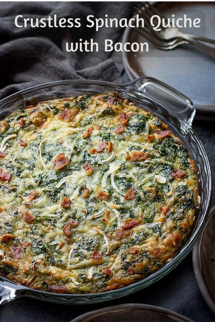 Crustless Spinach Quiche Recipe with Bacon in a handled glass pie plate on a dark napkin with handmade ceramic plates and silver forks.