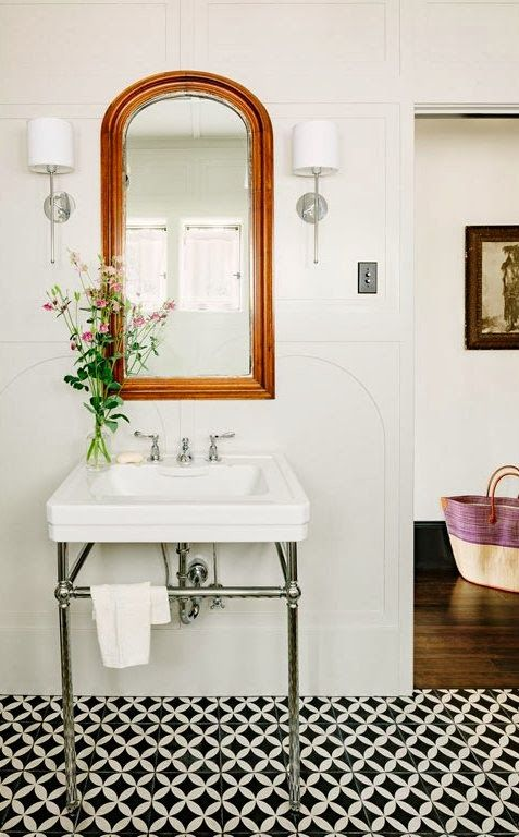 Small bathroom - tiles, a simple wash basin sink and arched mirror.