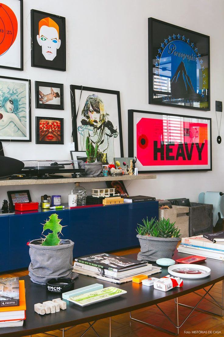 Essa sala de estar tem prateleira de concreto, móvel azul laqueado e parede com quadros.