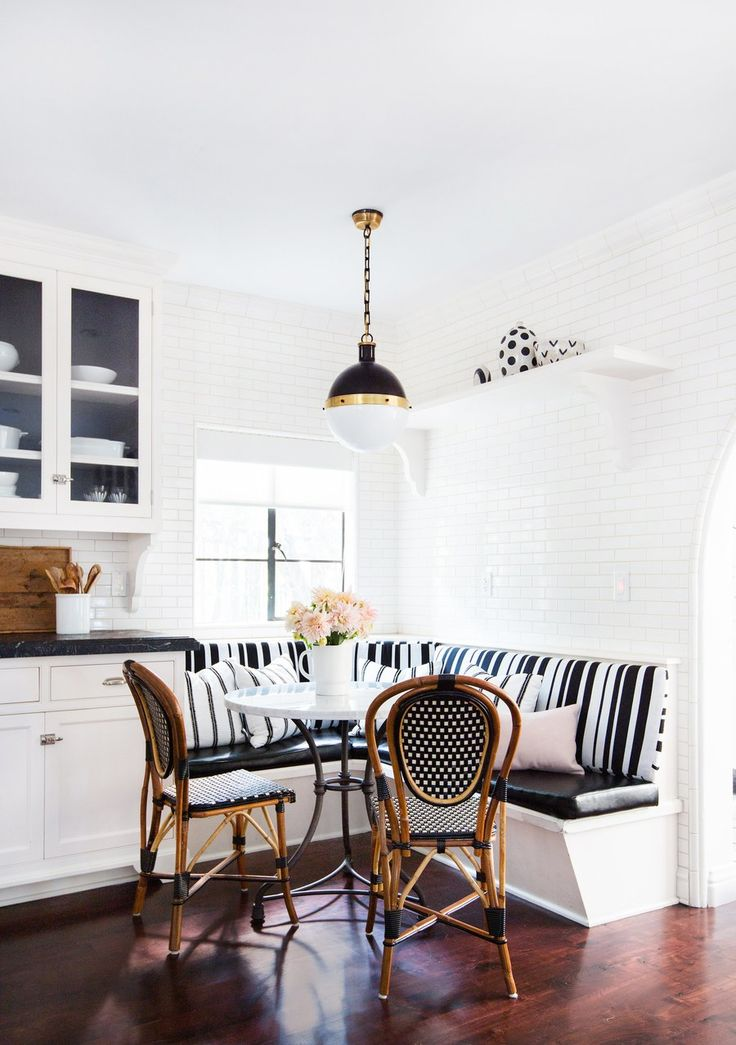 In the breakfast nook, a pendant from Circa Lighting dangles over a custom-made table by Consort Design and chairs from Maison Midi in Los Angeles. The polka-dot ceramics are by Matthew Ward.