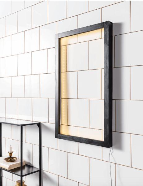 KARWEI | Een strakke zwarte lijst met verlichting in de binnenrand wordt een kunstwerk aan de muur. Je versterkt het effect met een grafisch patroon erachter
