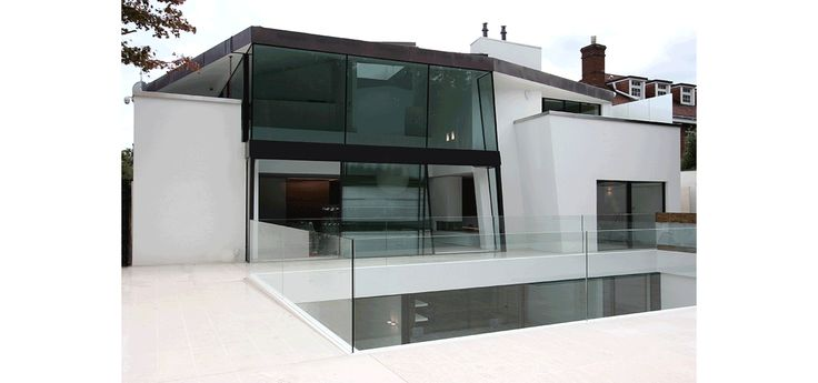 Double height glass box to rear of home with sliding glass doors to rear. Showing frameless balustrades around drop to basement courtyard