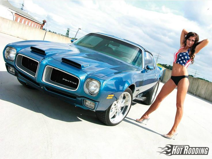 Sexy brunette in an American Flag top with a Pontiac Firebird.