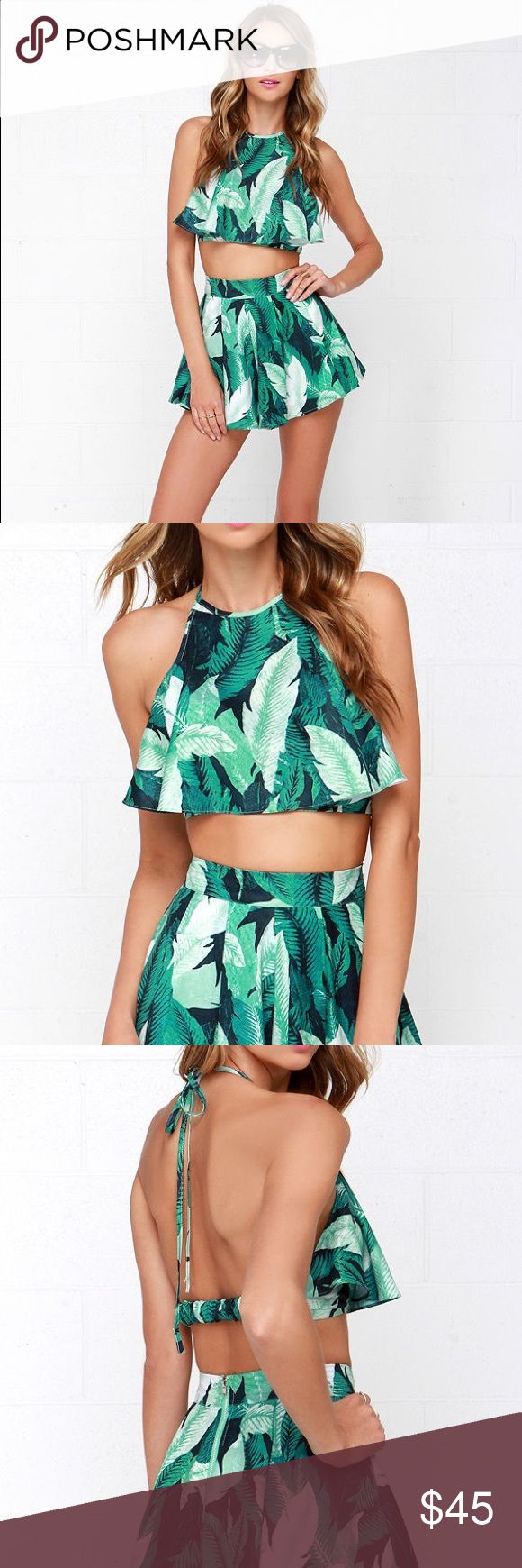 LEAF IT TO ME GREEN TROPICAL PRINT TWO-PIECE SET A vivid green tropical print covers the woven crop top of this flirty set, with a tying halter neckline, elasticized back strap, and a flouncy bodice. The matching shorty-shorts are topped with box pleats, and ruffle to a skirt-like finish. Shorts have exposed silver back zipper with clasp. This flirty and fun outfit is great for summer days, beach vacations, going out and honestly any other type of occasion! Lulu's Other
