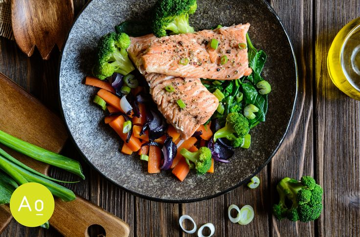 Fried salmon steaks with steamed carrot, broccoli, onion and spinach.
