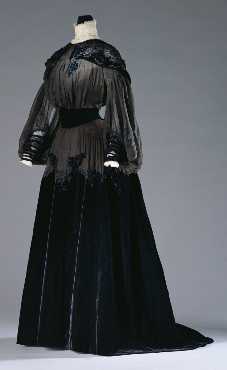Black silk chiffon and velvet day dress with embroidered net lace collar, by Jeanne Paquin, French, c. 1903. The hanging grape cluster decorations match the flowing dress lines. During the Art Nouveau period, motifs of organic natural objects were favored and often used as clothing ornaments.