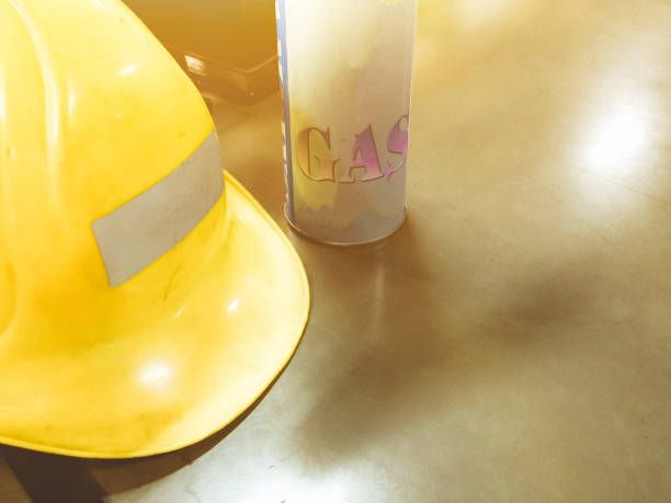 yellow dirty safety helmet and small can of gas on wooden table with