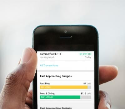 hand holding a mobile phone showing Mint's budgets' progress bars