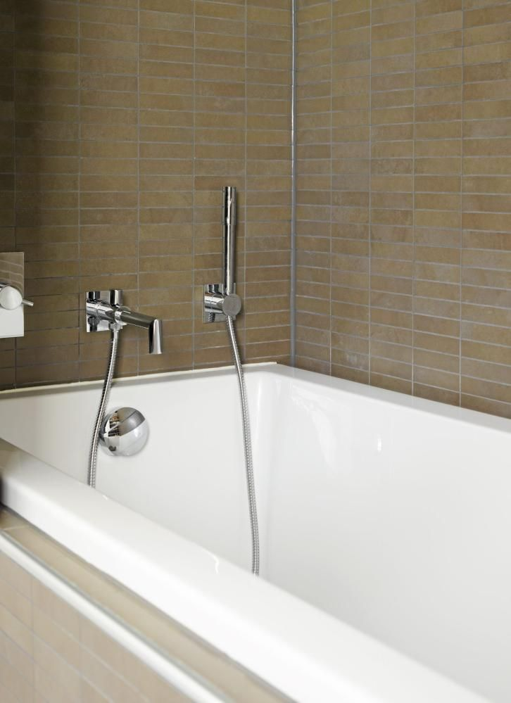 Badekaret er rammet inn av lekre fliser i duse bruntoner, og er med på å gjøre dette til et behagelig velværerom.