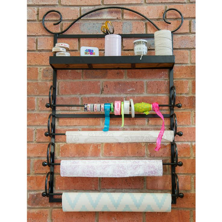 Store wrapping paper, ribbons, washi tape and more on the Deluxe Gift Wrap Station. The Gift Wrap Station is metal and includes handy wooden shelf.