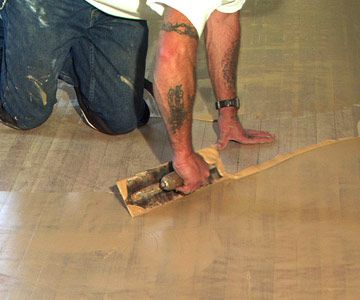 A paste made from sanding dust and lacquer sealer was troweled over the entire floor to fill any cracks between the boards. Using dust from the floor in the filler ensures that it will match the wood perfectly.