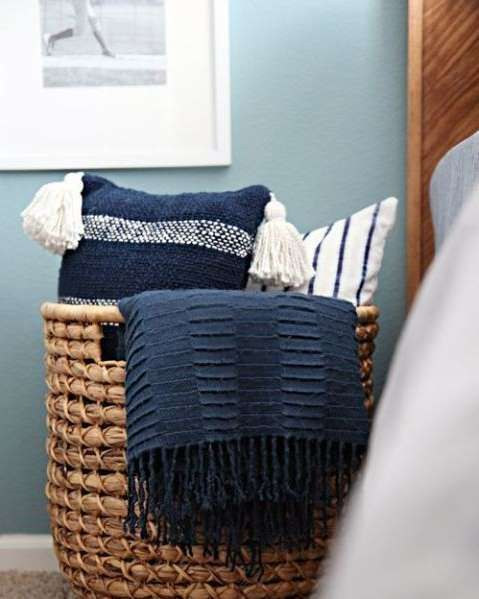 Throw pillows seem to have overtaken your bedroom? Use a wicker catch-all like the blogger behind I ... - I Heart Organizing