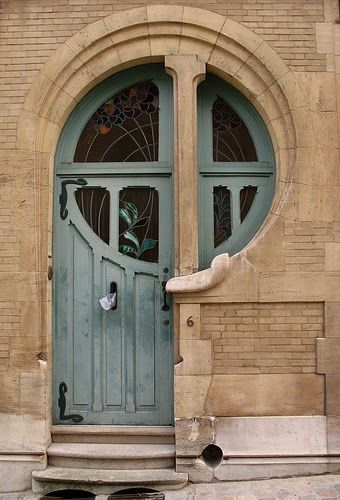 Porte Art Nouveau avec vitraux. Quelle forme étrange.   Si vous avez une porte d'entrée plus standard à remplacer, venez chiffrer votre projet sur http://www.avantages-habitat.com/travaux-fenetre-et-menuiserie-71.html