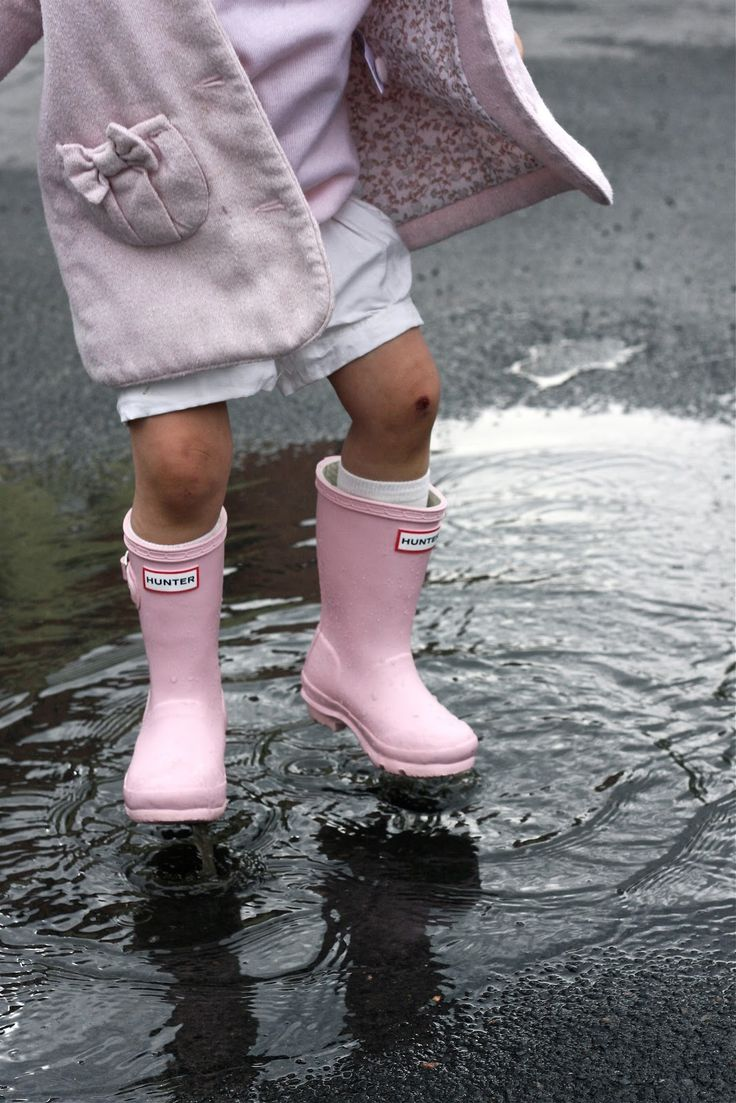 little girl in pink boots splashing in rain puddle