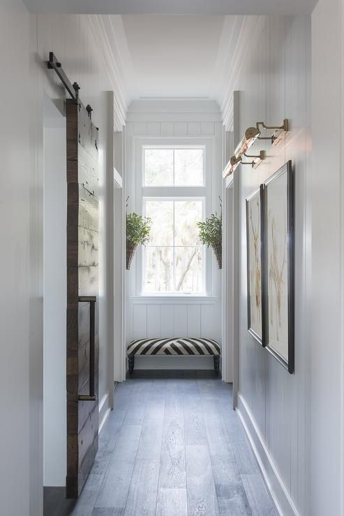 Chic hallway features vertical shiplap walls lined with side by side art illuminated by antique brass picture lights situated across from a plank barb door on rails.
