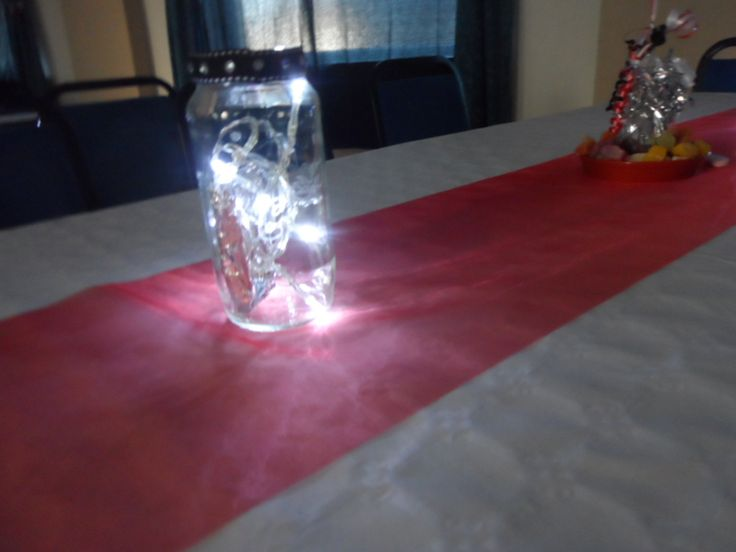 I engraved masks onto the jam jars.Ribbon around the tops with gems. Battery lights inserted to give a soft glow.