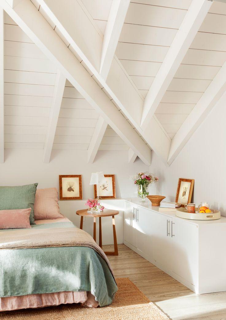 Dormitorio en buhardilla con envigado blanco, mueble bajo, cuadros y mesita redonda 00409158