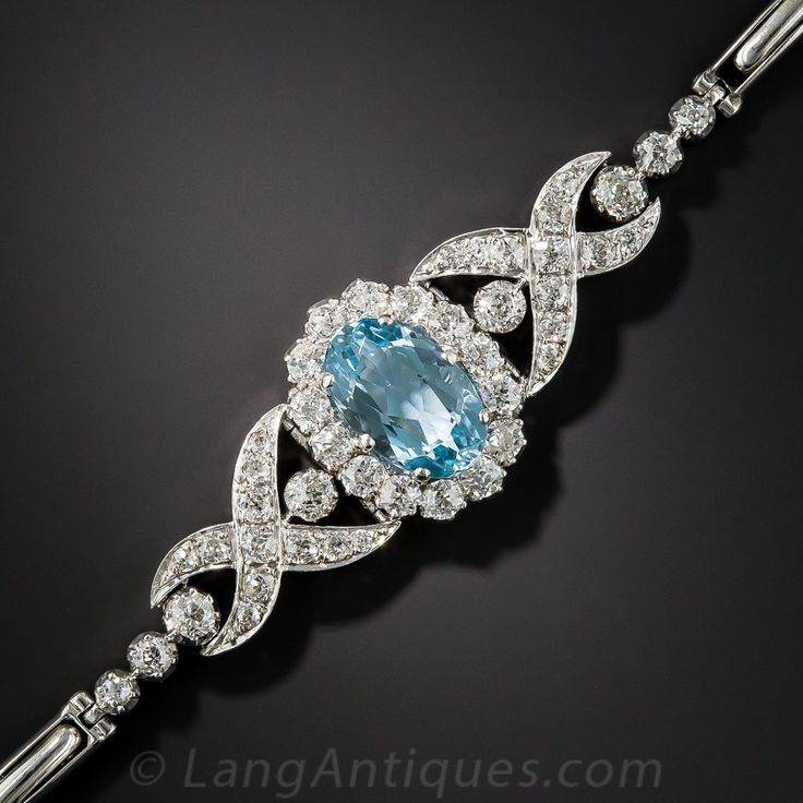 This truly rare (aquamarine bracelets from the period are few and far between) and ravishing Belle Époque jewel, masterfully handcrafted in platinum, circa 1910-1920, glistens front and center with an enchanting sky blue oval aqua, set within a glittering halo of bright white old mine-cut diamonds. The scintillating centerpiece is embraced on each side with stylized diamond-set 'Xs' transitioning to an expandable (from 6 to 7 inches) white gold bracelet strap. 2.20 carats t...