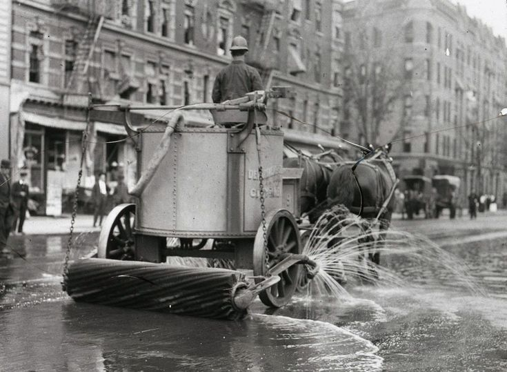 A two-horse team street cleaner, with sprayer, squeegee, and roller at rear.