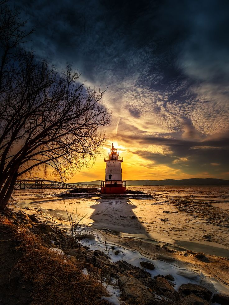 Sun is setting behind the little lighthouse located on the Hudson River in Tarrytown, NY. The river was almost completely frozen over.