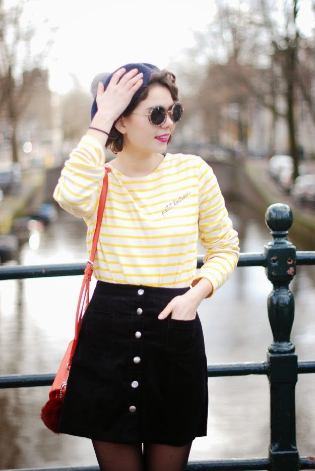 Yellow and white striped shirt. Dark skirt with buttons down the front