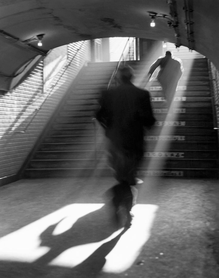 Sabine Weiss photography - .. Paris, 1955 ©  the shades/beans of light enveloping the figure as it ascends the staircase like Jesus rising to heaven