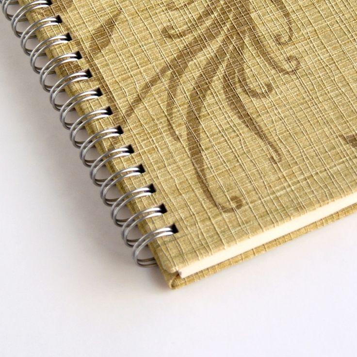 Detalle de una libreta hecha a mano reciclando un viejo muestrario de papel pintado con textura de tela.