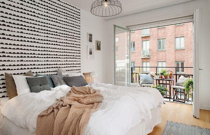 Idée déco chambre avec une chambre qui multiplie les points de vue entre son joli balcon mignon et sa tête de lit en papier peint Ferm Living à dunes