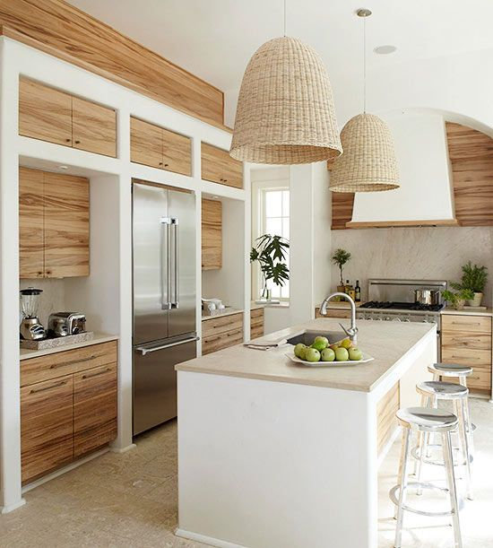 Two oversize pendant lights hang above this island and enhance the ambience of the room. The woven wicker shades contrast with the kitchen's sleek-lined aesthetic, and they also blend well with the stone flooring and the rustic wood grain on the cabinetry.