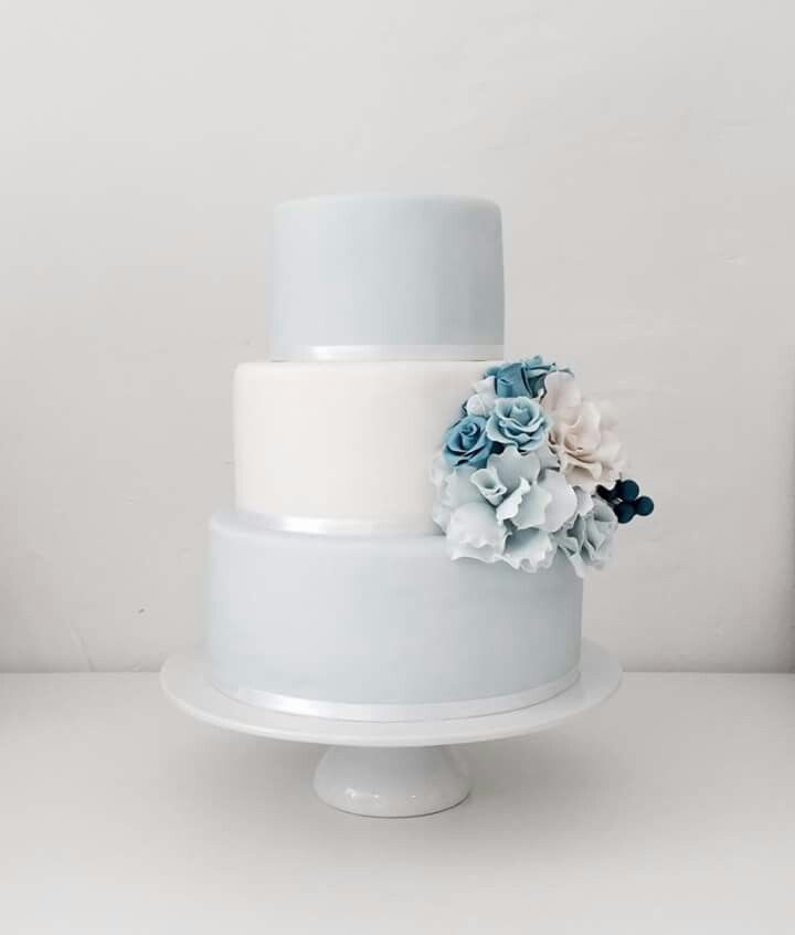 Blue and white tiered wedding cake with handmade flowers