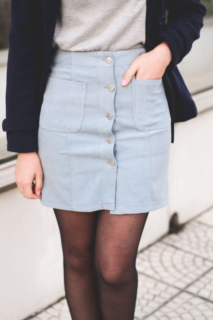 Look de inverno com casaco azul marinho, suéter cinza com estampa olhos, saia de cintura alta azul com botões na frente, meia calça preta e sapatilha boneca estilo retrô. Clique e saiba de onde são as peças!